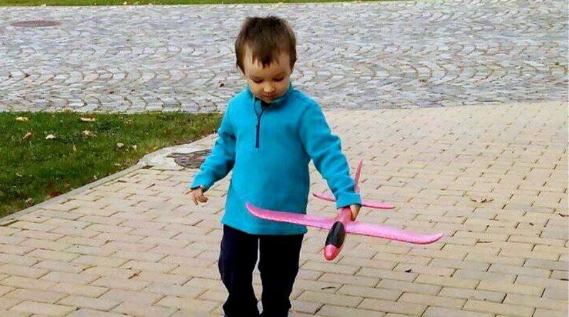 Момченце със самолет на тротоара