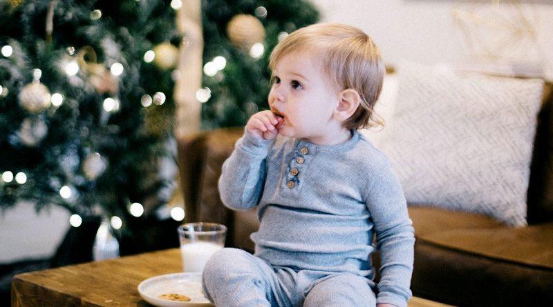 Малко дете, яде бисквита на маса до коледна елха