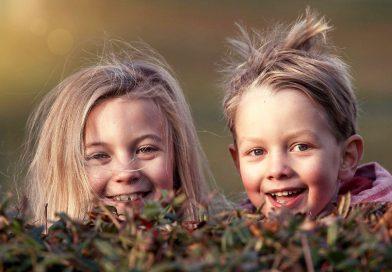 Усмихнати деца, момиче и момче, в есенен парк